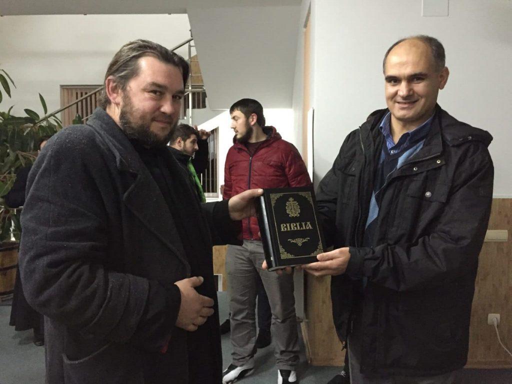 Preot Octavian Solomon dăruiește Biblia în traducere ortodoxă pastorului Vasile Filat la Biserica Bunăvestirea din Chișinău